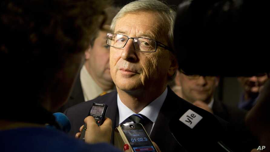 Leader of the Christian Democrat party Jean-Claude Juncker speaks with the media at his election headquarters in Luxembourg on Sunday, Oct. 20, 2013.