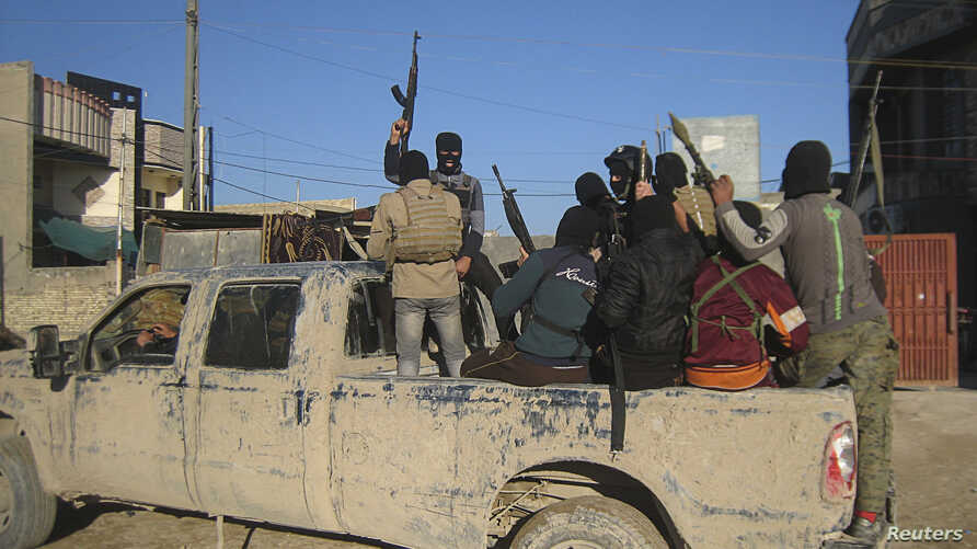 Masked Sunni gunmen, likely belonging to the group Islamic State of Iraq and the Levant (ISIL), are seen in the city of Falluja Feb. 8, 2014.