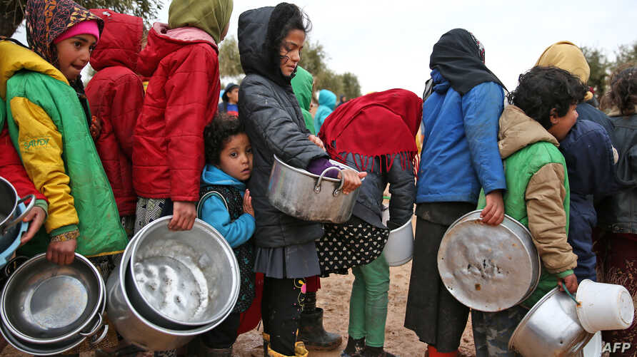 Syrian children queue to receive food distributed by humanitarian aid workers at a makeshift camp for displaced people, near the village of Yazi Bagh, about six kilometres from the Bab al-Salamah border crossing between Syria and Turkey in the north