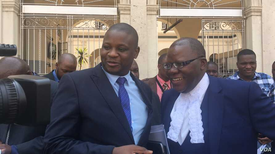 Tendai Biti, (R), opposition leader and member of Zimbabwe Lawyers for Human Rights, and Dzimbabwe Chibga from the rights group talk to reporters outside the High Court in Harare, Zimbabwe, September 2016. The two represented Zimbabwean opposition pa
