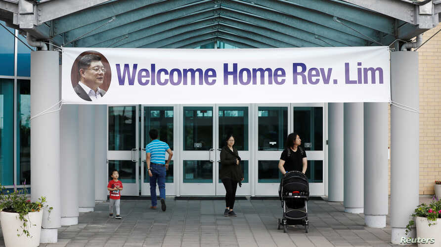 People walk under a welcome home sign for Pastor Hyeon Soo Lim, who returned to Canada from North Korea after the DPRK released Lim on August 9 after being held for 17 months, at the Light Presbyterian Church, in Mississauga, Ontario, Canada, Aug. 12