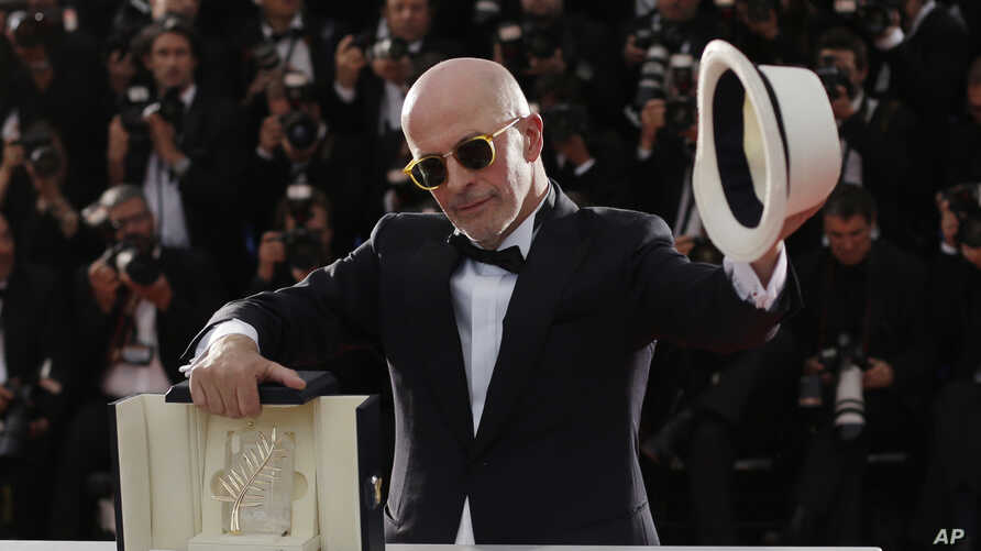 Director Jacques Audiard holds the Palme d'Or award for the film Dheepan as he poses for photographers during a photo call following the awards ceremony at the 68th international film festival, Cannes, southern France, Sunday, May 24, 2015.