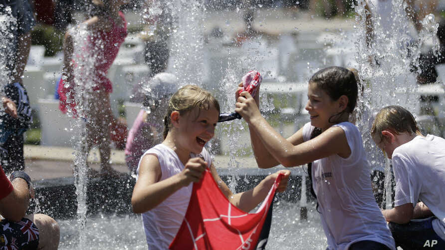 Children play in the fountain in the scorching heat at the Australian Open tennis championship in Melbourne, Australia, Thursday, Jan. 16, 2014.