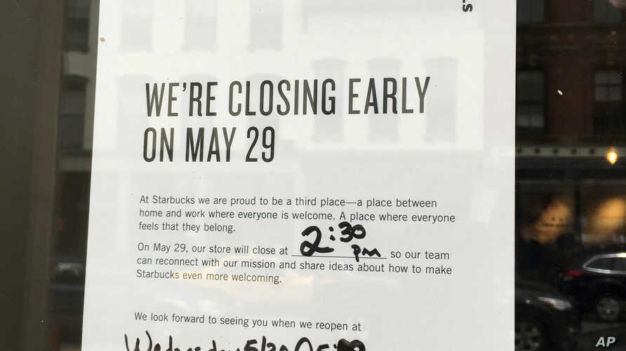 This May 27, 2018 photo shows a sign displayed at a Starbucks cafe in Portland, Maine, reminding customers that the store will be closed Tuesday for training.