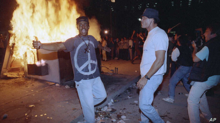 FILE - Demonstrators protest the verdict in the Rodney King beating case in front of the Los Angeles Police Department headquarters, April 29, 1992, in Los Angeles.