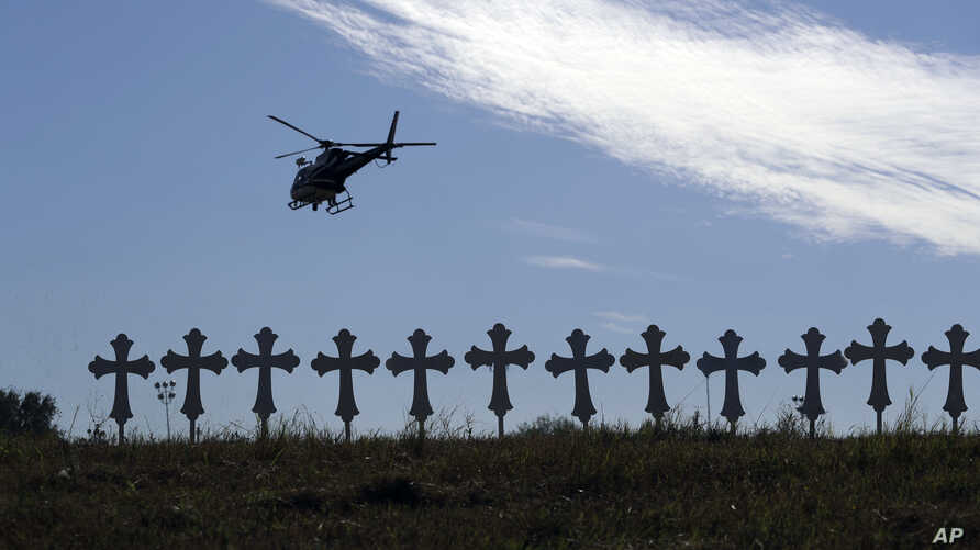 A law enforcement helicopter flies over crosses placed near the scene of a shooting at the First Baptist Church of Sutherland Springs in Sutherland Springs, Texas, Nov. 6, 2017.