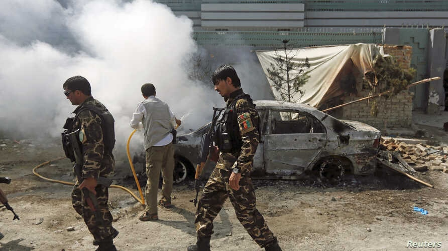 Afghan security forces walk past a burning car after a group of Taliban insurgents stormed a compound used by Afghanistan's intelligence agency in Kabul, Afghanistan, July 7, 2015.