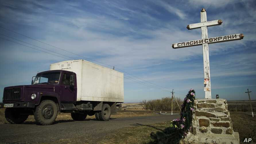 A truck drives by an Orthodox cross with a sign reading Save and Guard, at a memorial to the victims of the Malaysian Airlines MH17 plane crash,  near the village of Hrabove, eastern Ukraine, October 13, 2015 .