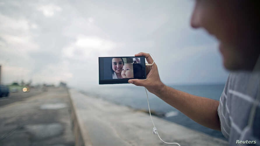 Artist Dariel Llerandis, 31, shows his wife and his 6-month-old daughter who live in Miami, as he speaks to them using the internet at a Wi-Fi hotspot in Havana, Sept. 22, 2015.