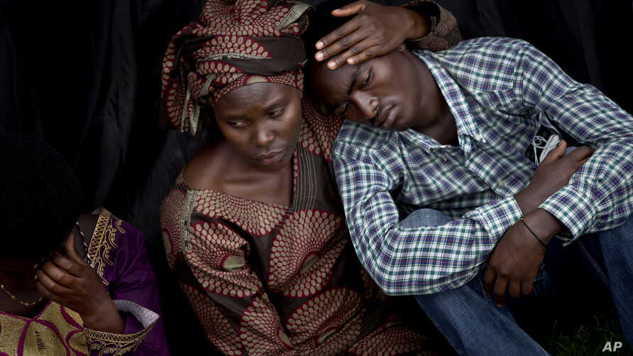 Bizimana Emmanuel, who was born two years before the genocide, is consoled by an unidentified woman while attending a ceremony to mark the 20th anniversary of the Rwandan genocide, at Amahoro stadium in Kigali, Rwanda, April 7, 2014.