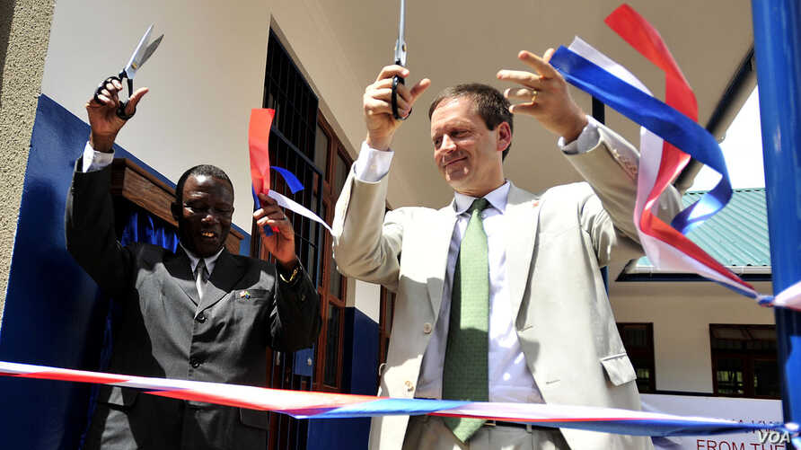 FILE - U.S. Ambassador to Tanzania, Mark Green, right, cuts a ribbon during a dedication ceremony at Jitegemee Secondary School in Dar es Salam, Tanzania, Dec. 18, 2008.