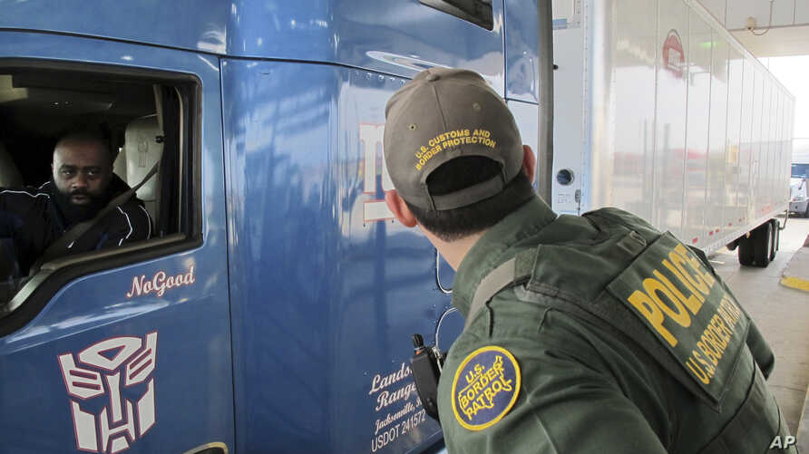 FILE - Border Patrol agent Eric Mendoza speaks to the driver of a tractor-trailer waiting to pass through the Laredo North vehicle checkpoint in Laredo, Texas, on Feb. 2, 2018.