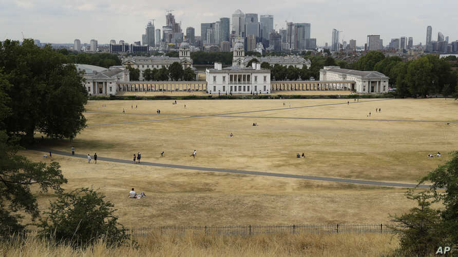 FILE - A view shows parched grass from the lack of rain in Greenwich Park, backdropped by the Royal Museums Greenwich and the skyscrapers of the Canary Wharf business district, during what has been the driest summer for many years in London, July 24,