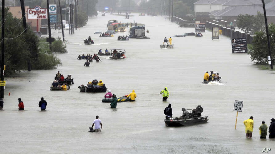 Rescue boats fill a flooded street as flood victims are evacuated as floodwaters from Tropical Storm Harvey rise  Aug. 28, 2017, in Houston.