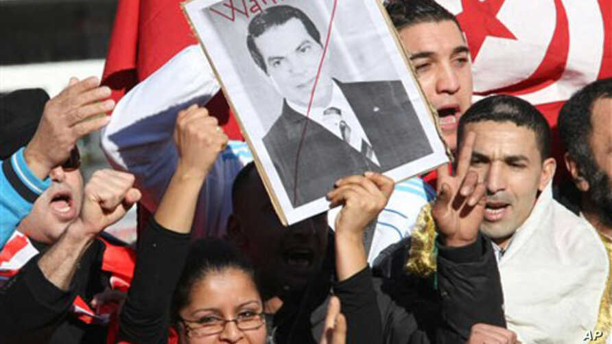 """A woman holds a picture of Tunisia's deposed leader Zine El Abidine Ben Ali, reading """"Wanted"""", during a demonstration showing solidarity with Tunisians, in Marseille, southern France , Jan. 15, 2011. Unrest engulfed Tunisia on Saturday after a popula"""