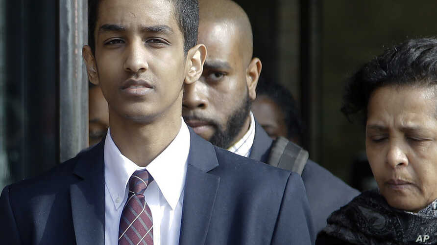 Robel Phillipos, left, departs federal court after he was convicted in Boston on two counts of lying about being in the dorm room of Boston Marathon bombing suspect Dzhokhar Tsarnaev three days after the bombing in 2013, Oct. 28, 2014.