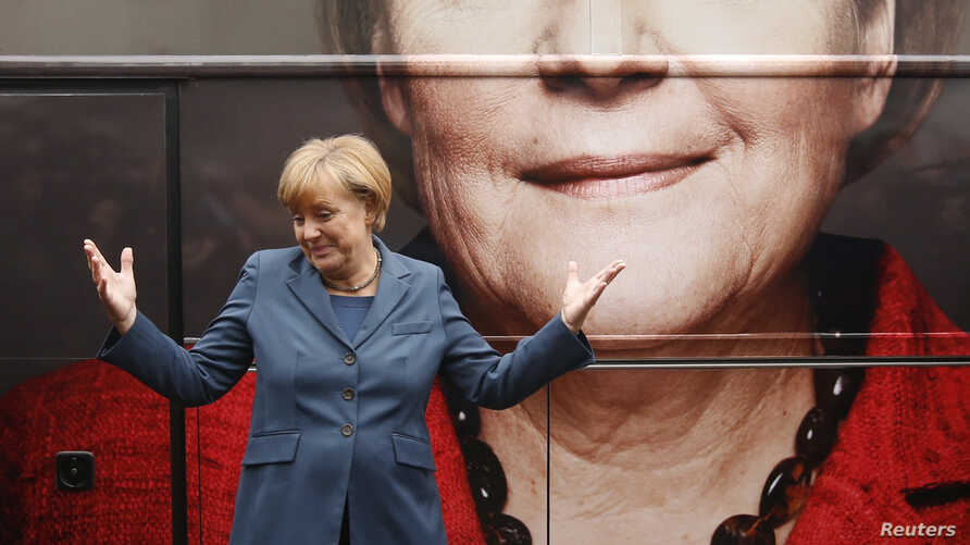 German Chancellor Angela Merkel and leader of the Christian Democratic Union party CDU stands in front of her election campaign tour bus before a CDU board meeting in Berlin, Sept. 16, 2013.