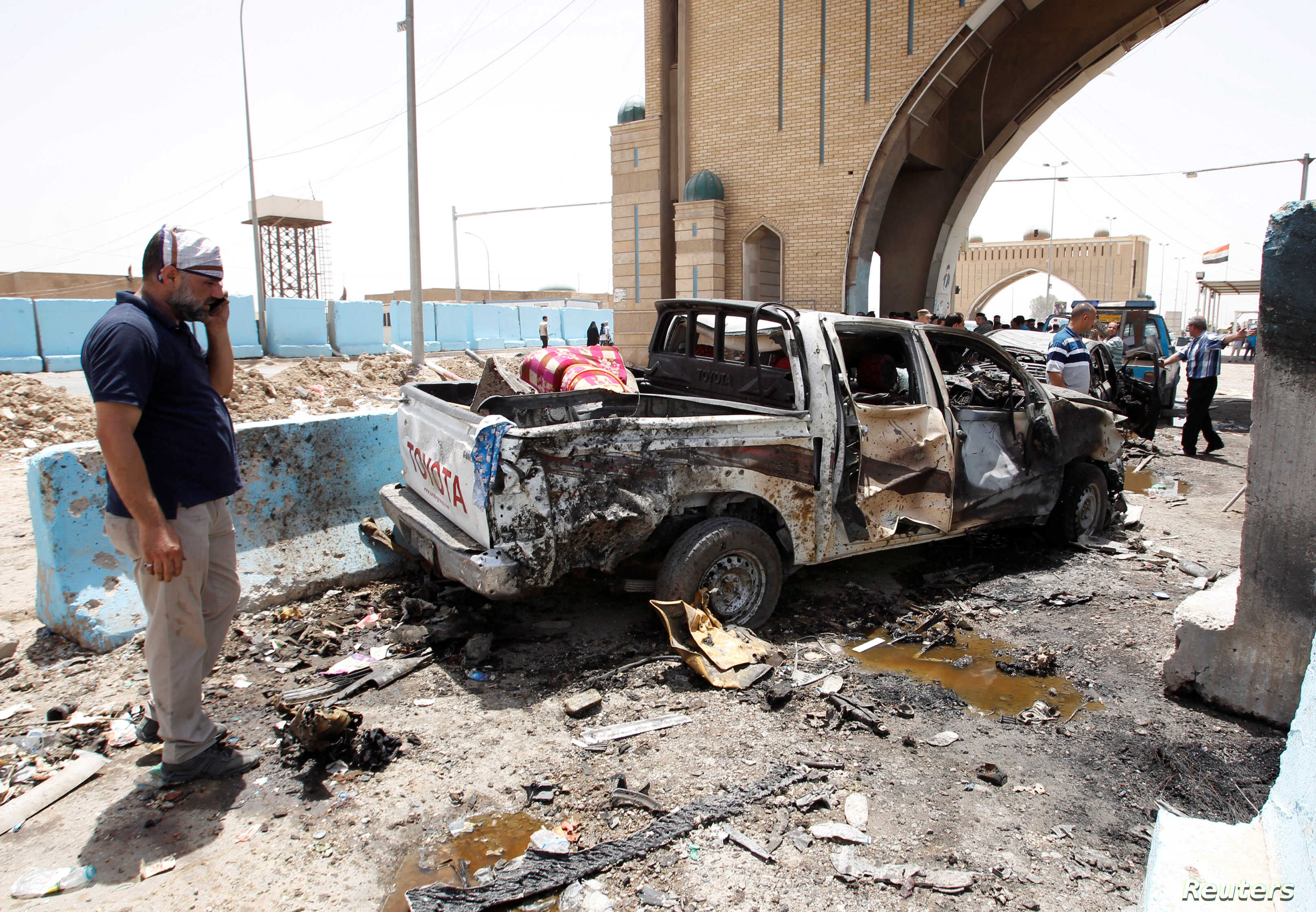 A man stands at the site of a suicide bomb attack at a checkpoint in Rashidiya, a district north of Baghdad, Iraq on July 13, 2016.