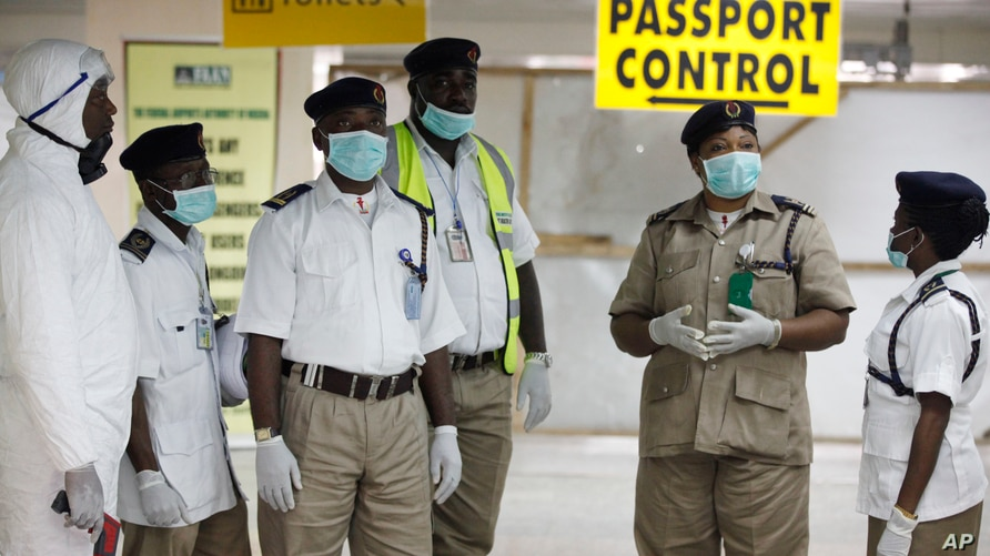 Nigeria health officials wait to screen passengers at the arrival hall of Murtala Muhammed International Airport in Lagos, Nigeria, Monday, Aug. 4, 2014. Nigerian authorities on Monday confirmed a second case of Ebola in Africa's most populous countr