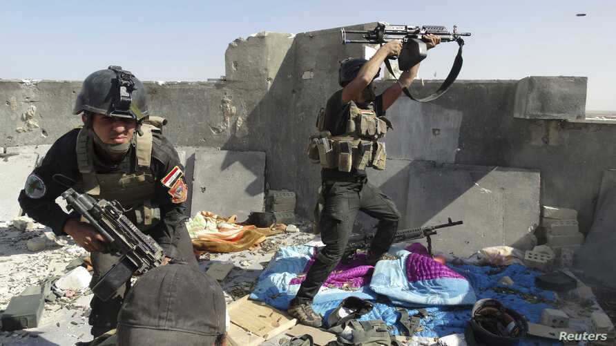Members of the Iraqi Special Operations Forces take their positions during clashes with the Islamic State of Iraq and the Levant in Ramadi, Iraq, June 19, 2014.