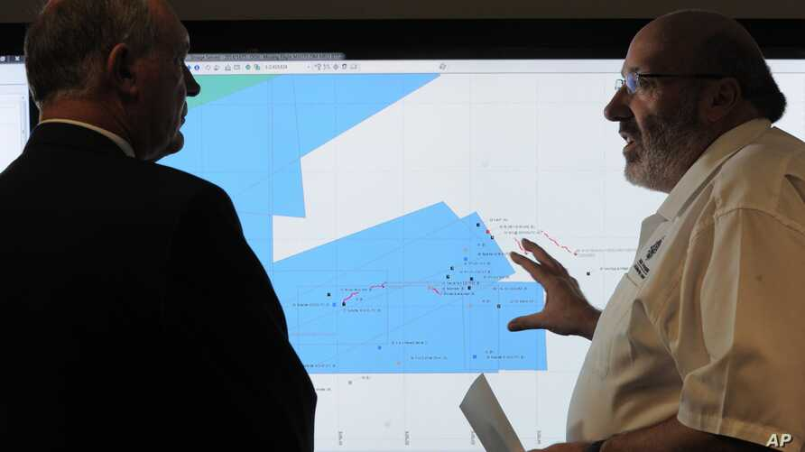 Mike Barton, rescue coordination chief, right, shows Australia's Deputy Prime Minister, Warren Truss, the map of the Indian Ocean search areas during a tour of the Australian Maritime Safety Authority's rescue coordination center in Canberra, Sunday,