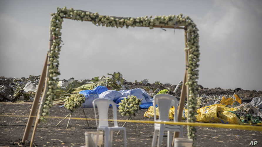 Wreaths and floral installations stand next to piles of wreckage at the scene where the Ethiopian Airlines Boeing 737 Max 8 crashed shortly after takeoff on Sunday killing all 157 on board.