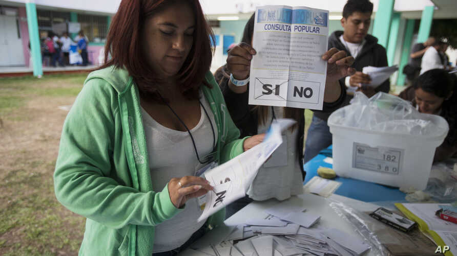 """An electoral worker shows a ballot marked """"yes,"""" during a plebiscite concerning a border dispute with Belize, in Guatemala City, April 15, 2018"""