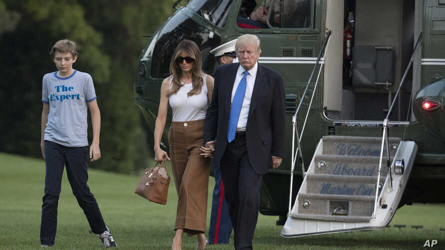 President Donald Trump, first lady Melania Trump, and their son and Barron Trump walk from Marine One across the South Lawn to the White House in Washington, June 11, 2017.