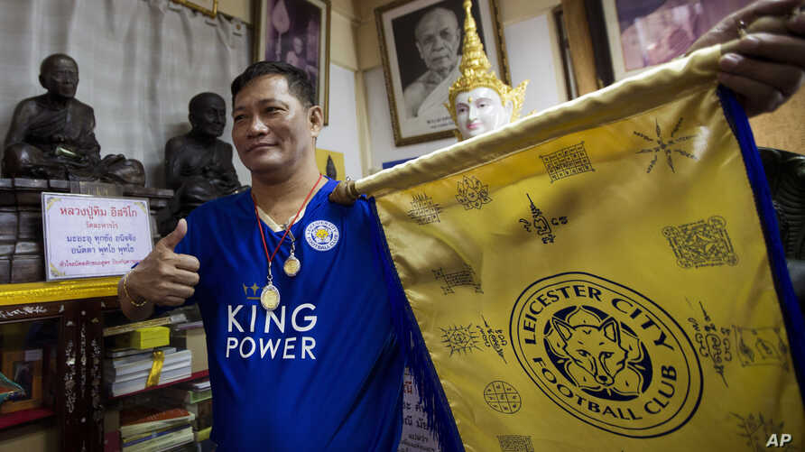 Korpsin Uiamsa-ard, a mentee of chief monk Phra Prommangkalachan at the Wat Traimitr Withayaram temple, holds up a Leicester City banner in Bangkok, Thailand, Tuesday, May 3, 2016.