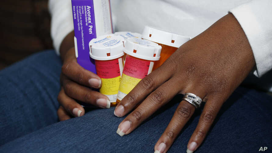 FILE - A patient holds the medications she takes to slow the progression of her multiple sclerosis, Feb. 24, 2015.