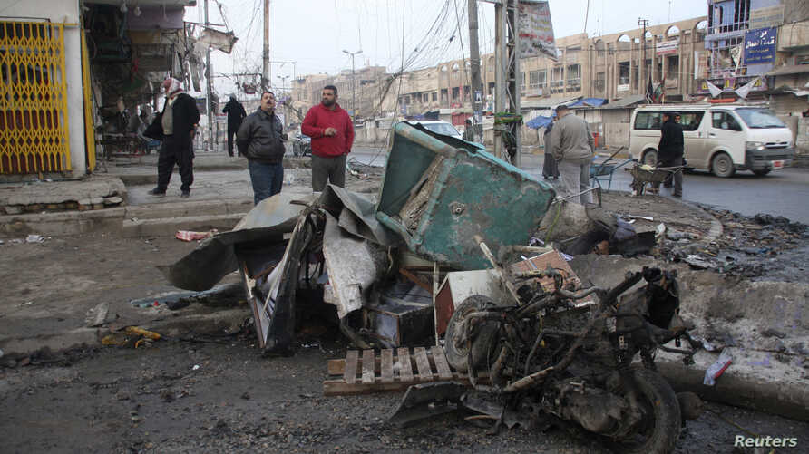 Residents inspect the site of a bomb attack in Baghdad, Jan. 14, 2014.