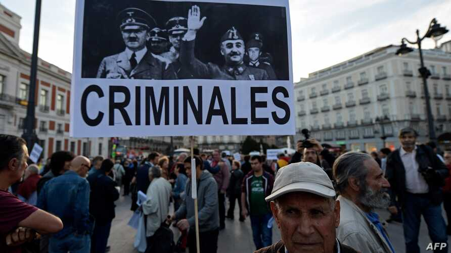 """A man holds a placard displaying pictures of Spanish late dictator Francisco Franco and Germany's late dictator Adolf Hitler during a demonstration titled """"NiValleNiAlmudena, Madrid sin Franco"""" (Madrid without Franco) in Madrid, Oct. 25, 2018, agains"""