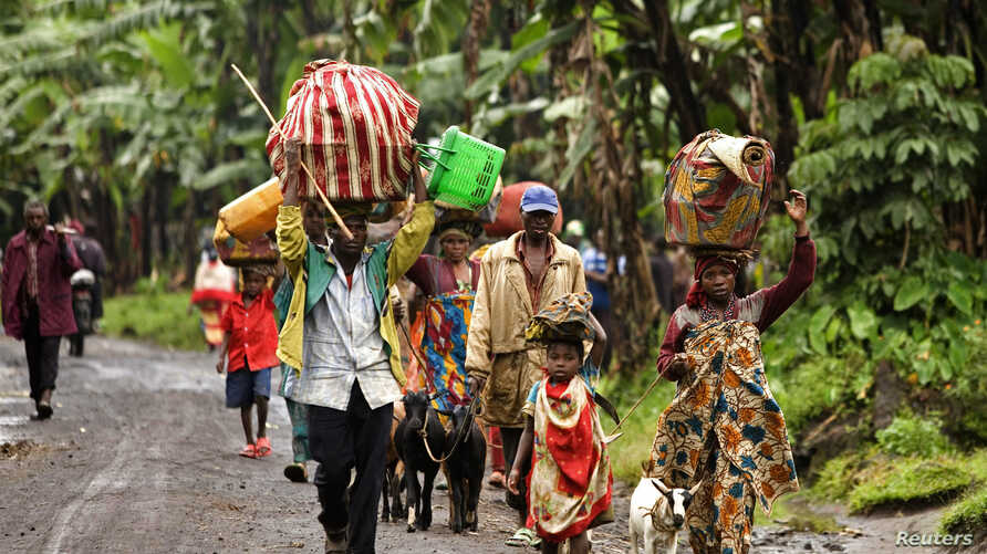 Internally displaced Congolese carry their belongings as they flee to safety, fearing renew clashes between the Congolese government forces and rebels in Kabindi, in the east region of the Democratic Republic of Congo, May 21, 2012.