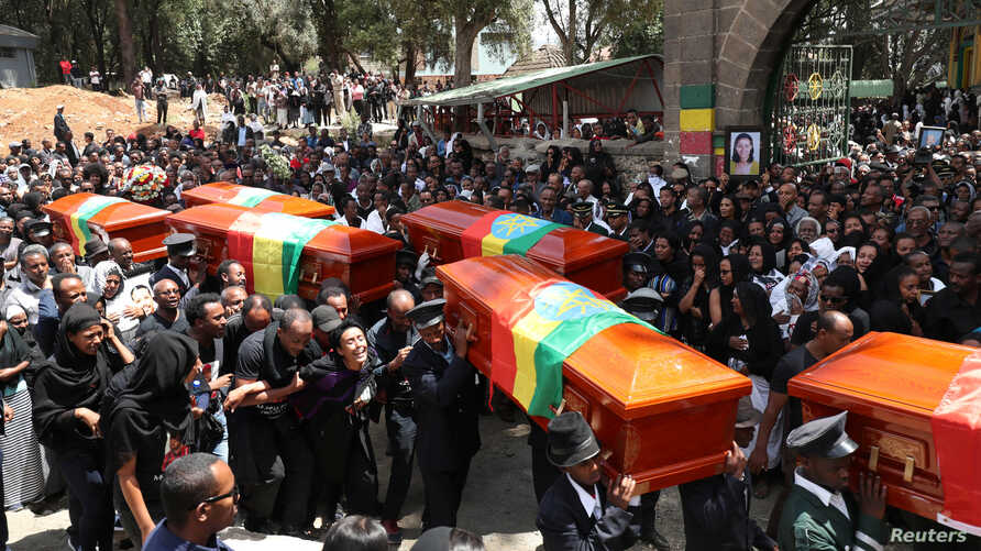 Pallbearers carry the coffins of the victims of the Ethiopian Airline Flight ET 302 plane crash, during the burial ceremony at the Holy Trinity Cathedral Orthodox church in Addis Ababa, Ethiopia, March 17, 2019.