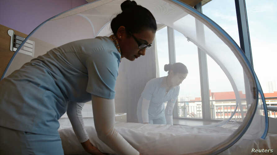 Nurses set up a mosquito tent over a hospital bed, as part of a precautionary protocol for patients who are infected by Zika at Farrer Park Hospital in Singapore Sept. 2, 2016