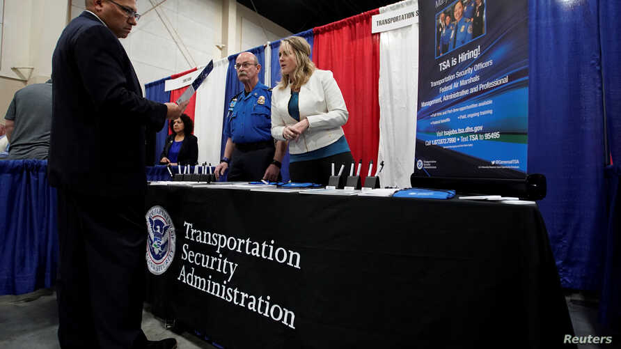 A veteran talks about job opportunities with a representative from Transportation Security Administration, TSA, at a military job fair in Sandy, Utah, U.S., March 26, 2019.