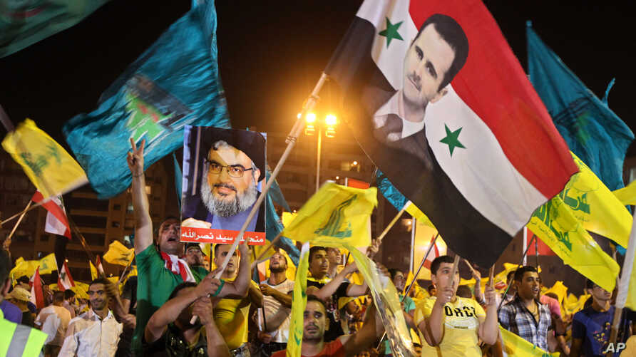 Hezbollah supporters wave Hezbollah and Syrian flags with a picture of Syrian President Bashar al-Assad, right, and Hezbollah leader Sheik Hassan Nasrallah, left, during a rally marking the sixth anniversary of the 2006 Israel-Hezbollah war, in Beiru