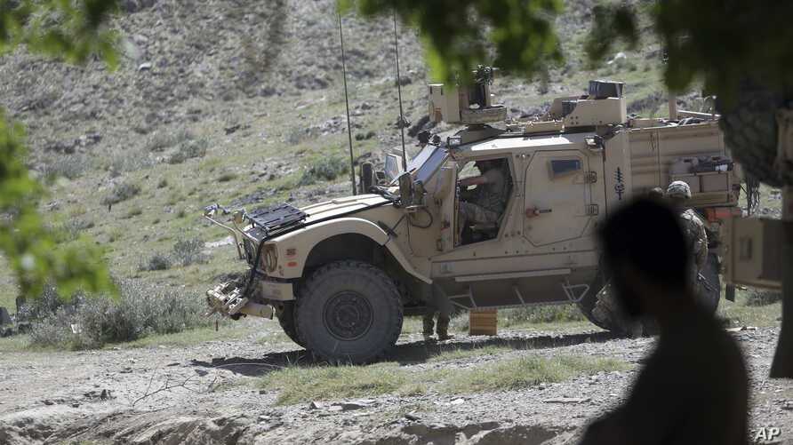 FILE - U.S. forces and Afghan commandos are seen in Asad Khil village in the Achin district of Jalalabad, Nangarhar province, Afghanistan, April 17, 2017.
