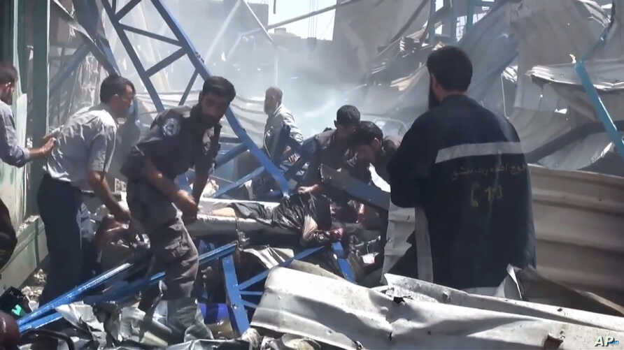 An image made from video posted online by the Shaam News Network, a loosely organized group opposed to Bashar Assad, Aug. 16, 2015, which has been verified and is consistent with other AP reporting, shows rescuers taking a victim from the site of Syr