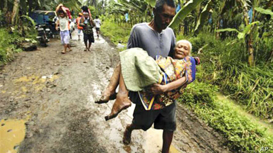 Rescuers and volunteers help an elderly woman to an evacuation center following flooding caused by the continued rains brought about by the cold front in the central and southeastern parts of the country, in southern Philippines, 18 Jan 2011