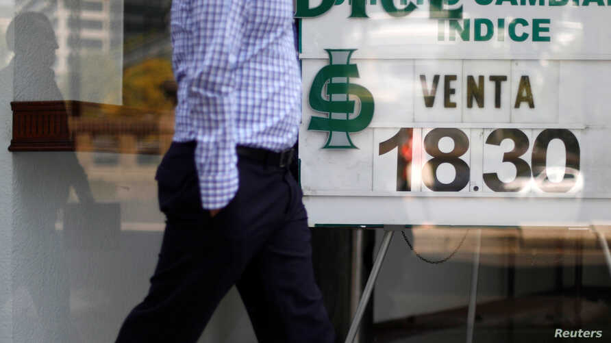 A man walks in front of a board displaying the exchange rate for Mexican peso and U.S. dollars at a foreign exchange house in Mexico City, Mexico, Oct. 20, 2017.