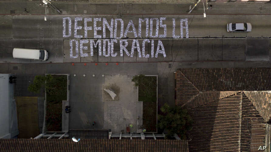 """Seen from above, a sign covering a street forms the Spanish phrase: """"We defend democracy,"""" made with photographs of the president and his cabinet, outside the Constitutional Court in Guatemala City, Jan. 9, 2019. Guatemala's highest court has blocked"""