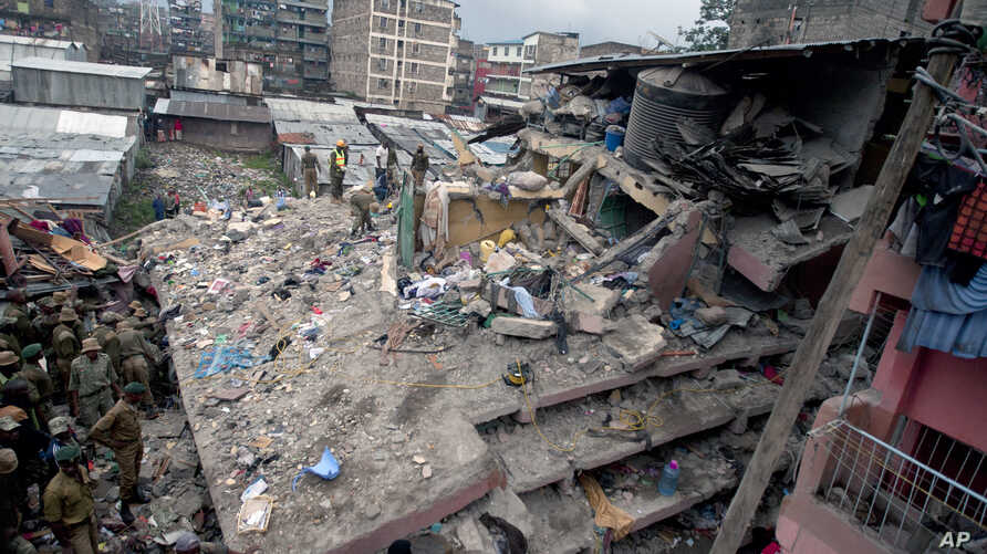 Kenyan police officers and Kenyan National Youth Servicemen search the site of a building collapse in Nairobi, Kenya, April 30, 2016.