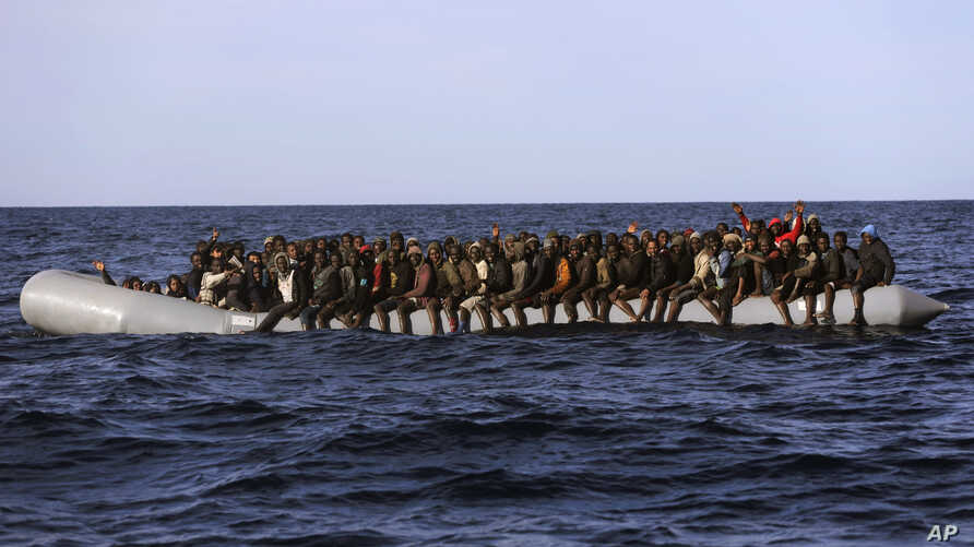 Sub-Saharan migrants crowd a rubber boat as they are rescued by members of Proactive Open Arms NGO, in the Mediterranean Sea, about 22 miles north of Zumarah, Libya, Jan. 27, 2017. Italy's coast guard, meanwhile, says it picked up about 1,000 migrant...