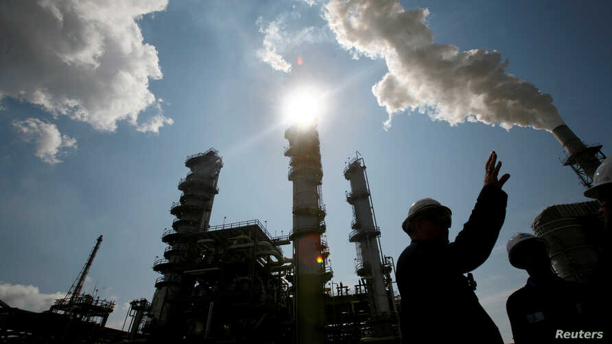 FILE - A worker at the Valero St. Charles Oil Refiner is seen in silhouette in Norco, Louisiana.