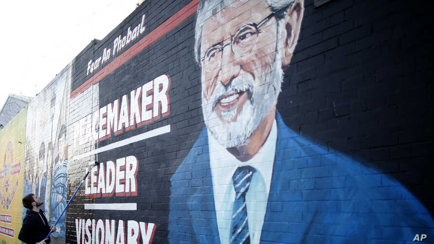 A man adds the finishing touch to a newly painted mural of Gerry Adams on the Falls Road, West Belfast, Northern Ireland, May, 2 2014.
