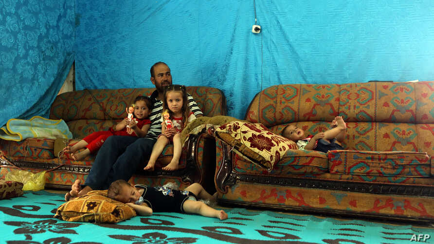 A Syrian refugee from Aleppo sits with his children in a makeshift tent in a Syrian refugee camp in the town of Kab Elias in Lebanon's Bekaa Valley, June 20, 2016.