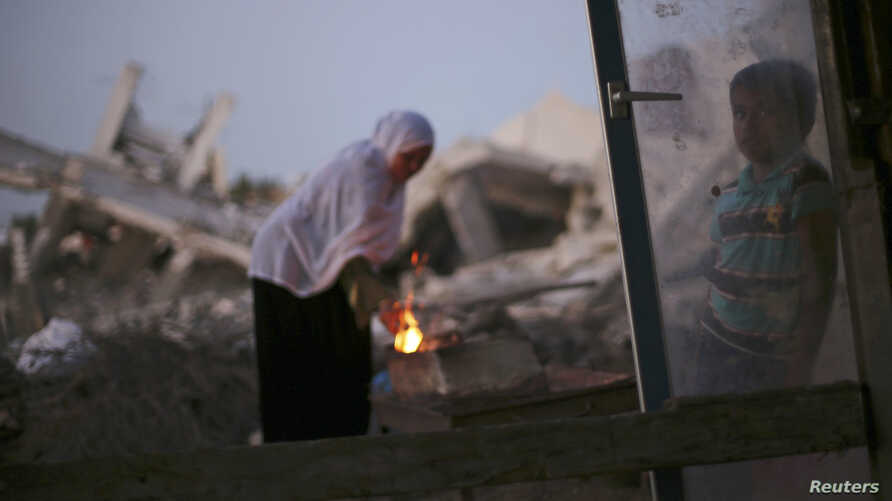 A Palestinian woman makes coffee on a fire outside her makeshift shelter near the ruins of her house, which witnesses said was destroyed during the Israeli offensive, in Al Mughraga village, south of Gaza City, Sept. 8, 2014.