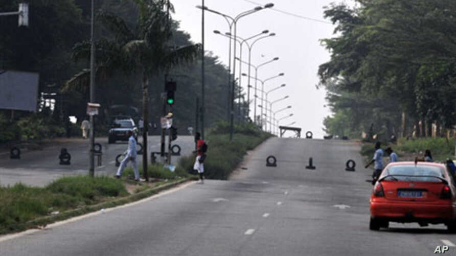People walk on a road blocked by armed forces near the Ivorian state television station in the Cocody district of Abidjan, 18 Dec 2010