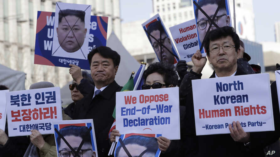 South Korean protesters and North Korean defectors hold portraits of North Korean leader Kim Jong Un during a rally urging the United States to discuss North Korean human rights issue in the upcoming summit between U.S. President Donald Trump and Nor
